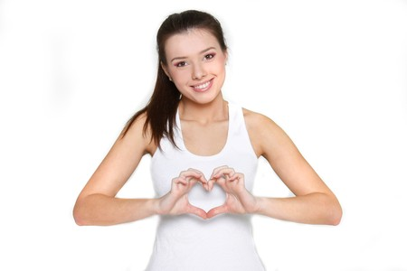 young beautiful girl showing heart symbol over white Stock Photo - 7770282