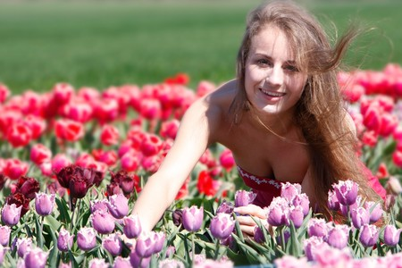 young happy girl in red and purple tulips photo