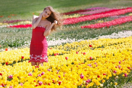 young beautiful girl in yellow and red tulips photo