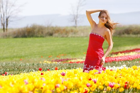 young beautiful girl in yellow tulips photo