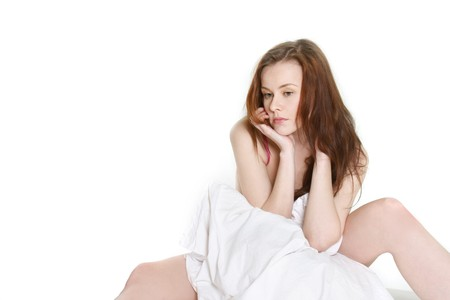 upset young woman in bed over white photo