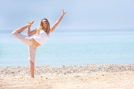 young girl doing gymnastics on beach photo