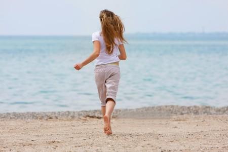 jong meisje lopen op strand
