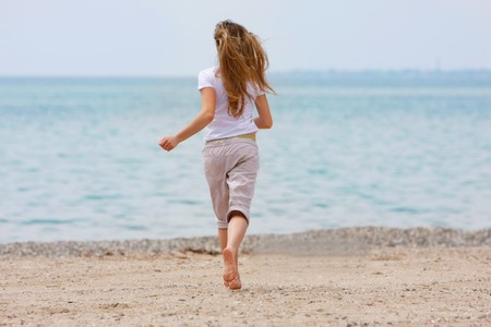 young girl running away on beach photo