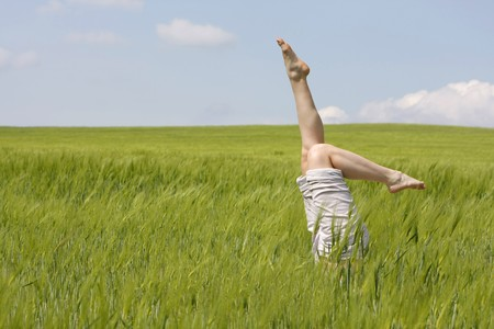 female legs raised up from green grass Stock Photo - 7786499