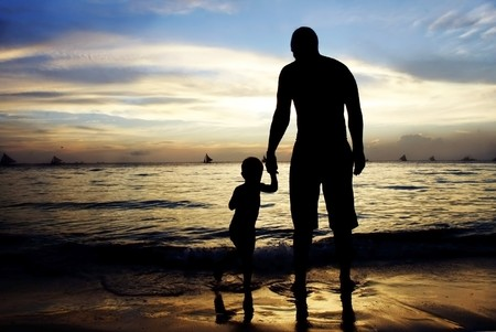natural love: father and son on sunset sea and sky background