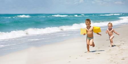 two kids running on beach photo