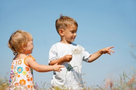 two kids playing with big dandellions photo