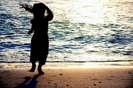 kid silhouette on sunset sea background