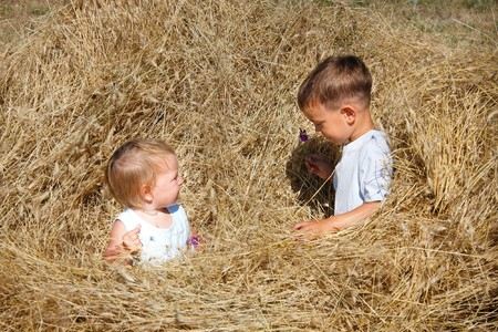 two kids playing in hay photo