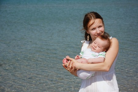 young mother and baby on sea background photo