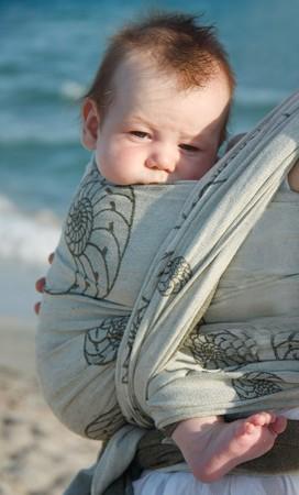 draagdoek: Portret van baby op zee achtergrond close-up