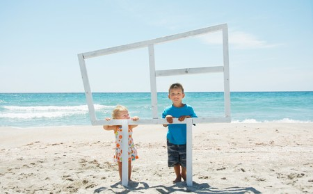 two kids looking out through wooden window on sea background photo
