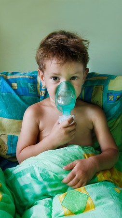 asthma: close up of child making inhalation
