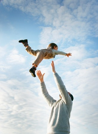 foster parenting: happy father and son playing on sky background