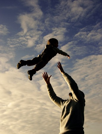 silhouettes of father and son playing on sky background photo