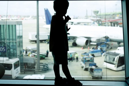silhouette of young boy on airport window background photo
