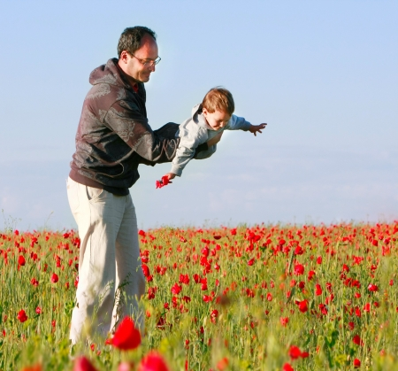 foster parenting: father and son playing on poppy field Stock Photo