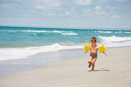 young boy running on beach photo
