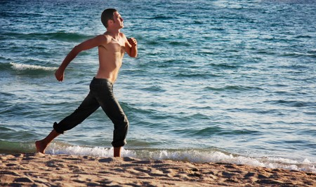 young man running on beach Stock Photo - 7804222