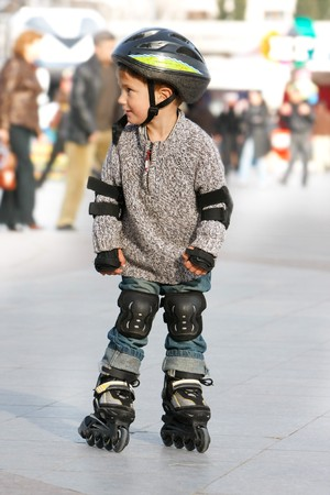 young boy rollerskating in city photo