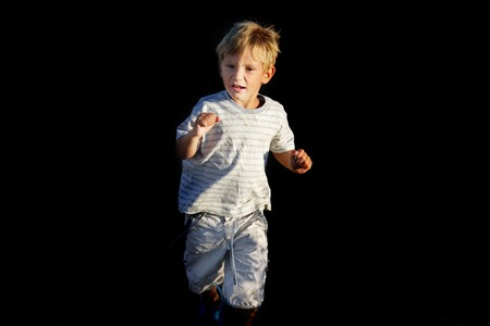scared boy running away over black Stock Photo - 7786531