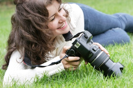 young smiling girl taking picture outdoors photo