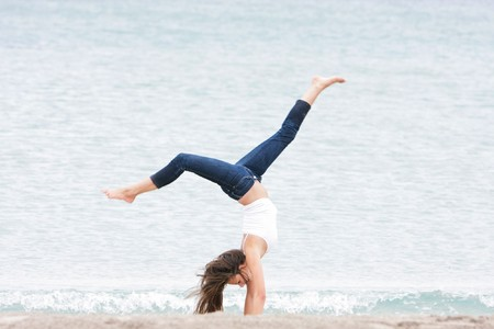 adolescence: young girl doing gymnastics on sea background
