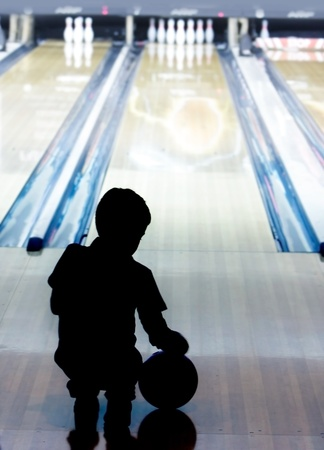 silhouette of young boy playing bowling photo