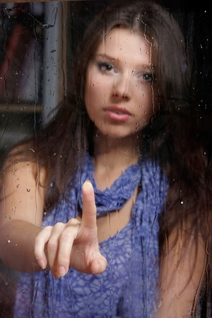 young sad woman behind wet window Stock Photo - 11943866