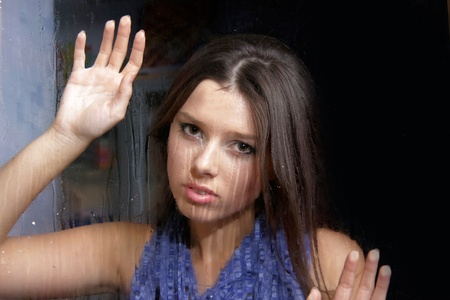 young sad woman behind wet window photo