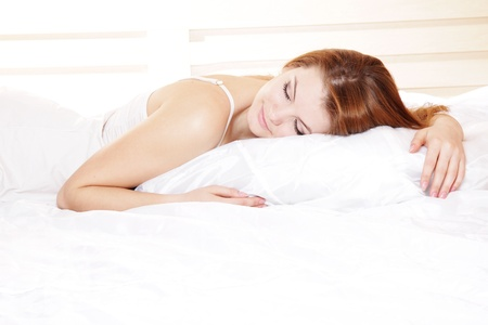 young beautiful woman sleeping in bed photo