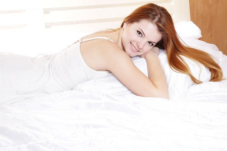 young smiling woman in bed photo