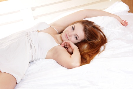 young happy woman in bed photo
