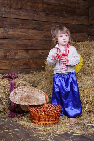 hayloft: cute child in traditional eastern european clothes on hayloft