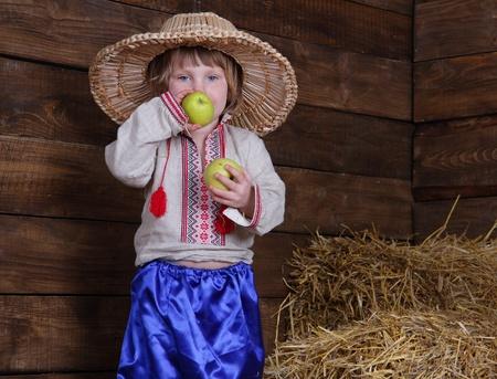 hayloft: ni�o lindo en la ropa tradicional de Europa del Este en el pajar