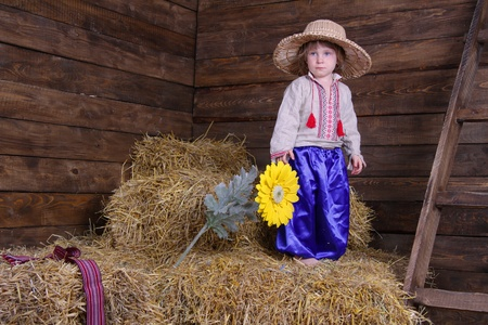 cute child in traditional eastern european clothes on hayloft photo