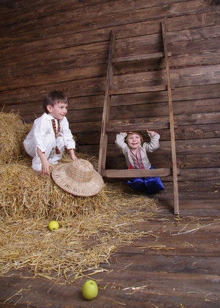 two kids in traditional eastern european clothes on hayloft photo