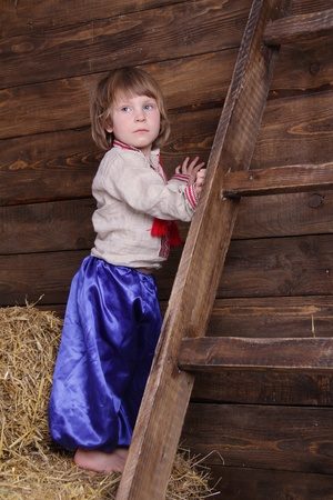young cute child in traditional eastern european clothes on hayloft photo