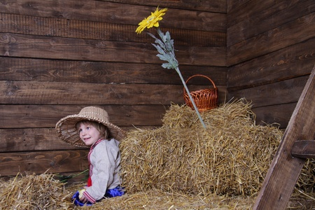young happy child in traditional eastern european clothes on hayloft photo