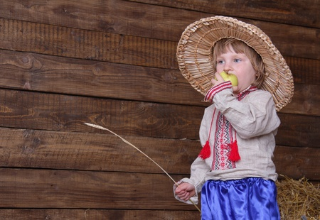 cute child in eastern europe traditional costume in hayloft photo