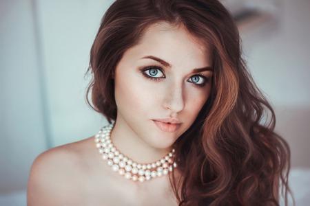 Hermosa mujer joven con los ojos azules en el collar de perlas Foto de archivo