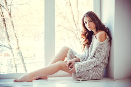 Beautiful young woman with blue eyes and bare legs sitting near window