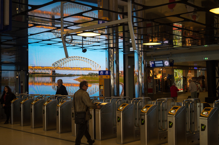 lock: Tourniquets gates and Check-in columns at Amsterdam Centraal Railway Station The Netherlands.