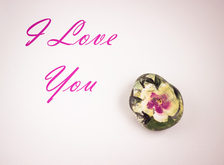 flower painted on small pebble, rock, white background, i love you text