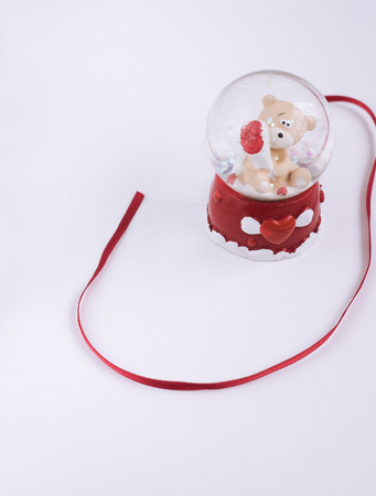 bear with bouquet in crystall ball an red ribbon closeup