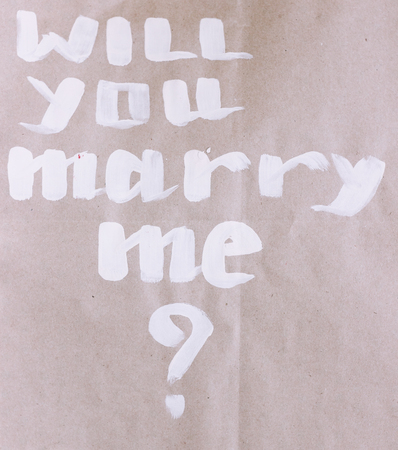 white will you marry me text on brown background proposal question