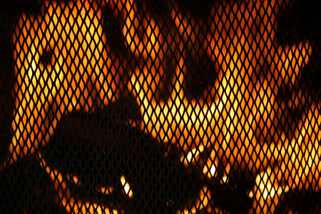 behind bars: Brightly blazing fire behind bars rustic fireplace.