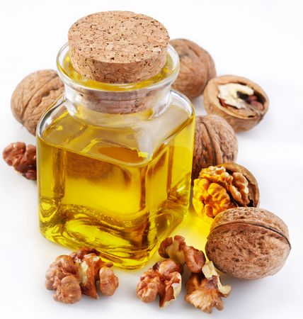 Walnut oil with nuts on a white background photo