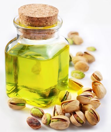 Pistachio oil with nuts on a white background photo
